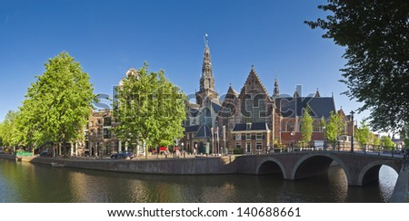 Oude Kerk Church (14th Century) bathed in warm early sunlight, residing in the heart of the city and neighbour to Amsterdam's red light district. - stock photo