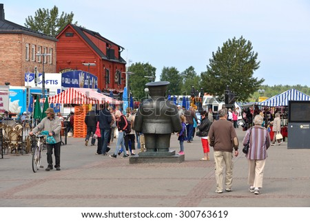 """OULU, FINLAND - JULY 13,2015:Market Square is hub of activity during summer. All comings and goings are supervised by """"Bobby at Market Place"""". This statue stands in front of Hall in honour of officers - stock photo"""