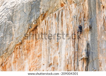 oung man climbs on a rocky wall - stock photo