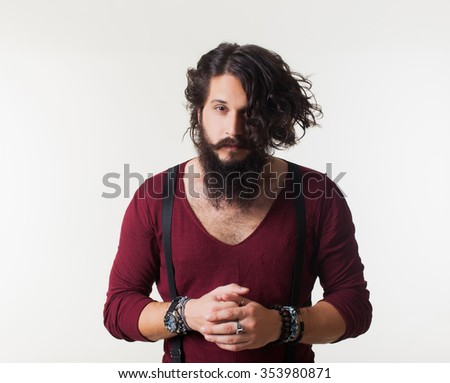 oung man in a red jacket and trousers with a beard and mustache braces posing in the studio on a white background, the macho male muscular guy, handsome brutal man portrait male fashion clothing - stock photo