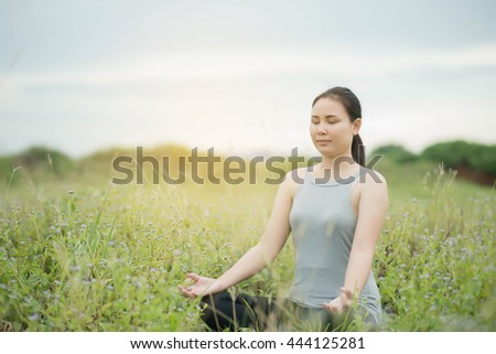 oung woman during relaxation and meditation in park meditation session. Frame shows half of body.