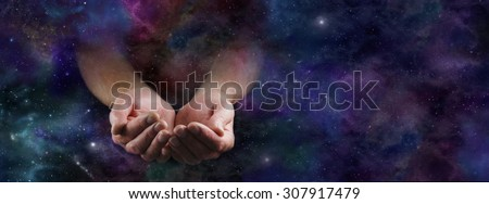 Our Abundant Universe - Male hands emerging from a wide dark deep space background gesturing with cupped hands - stock photo