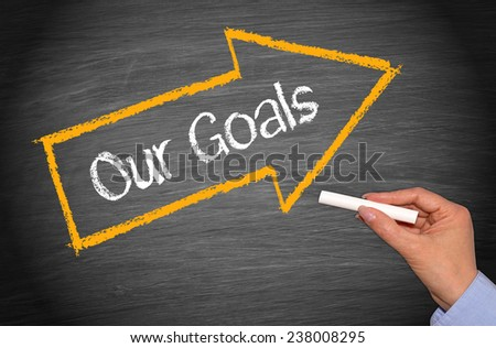Our Goals - Business concept with arrow and hand on chalkboard background - stock photo