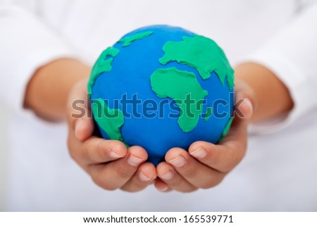 Our home - child holding earth globe made of clay - stock photo
