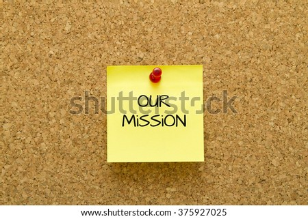 Our mission word written on a yellow sticky note on cork board