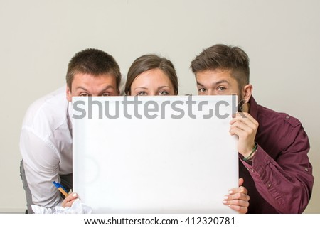 Our new project. Team hiding behind white board - stock photo
