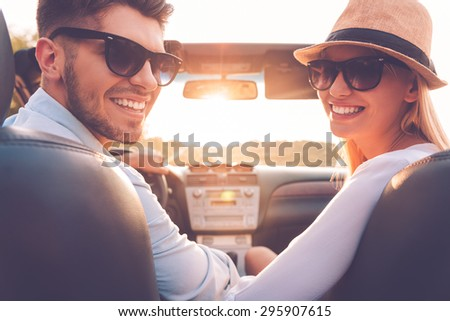 Our perfect weekend journey. Rear view of cheerful young couple looking over shoulder and smiling while sitting inside of their convertible  - stock photo
