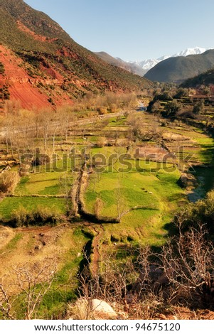 Ourika valley green fields and red rocks over river - stock photo