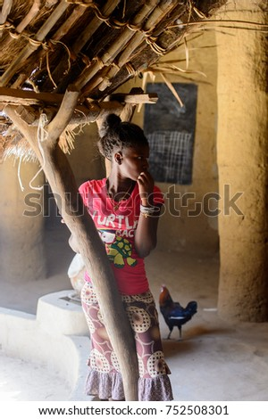 OUSSOUYE, SENEGAL - APR 30, 2017: Unidentified Senegalese woman with braids in pink shirt and skirt sits in the Diola house, the example of traditional African sculptural architecture