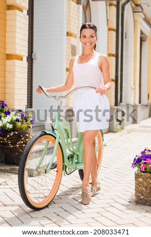 Out for a ride. Full length of attractive young smiling woman walking with bicycle along the beautiful street - stock photo