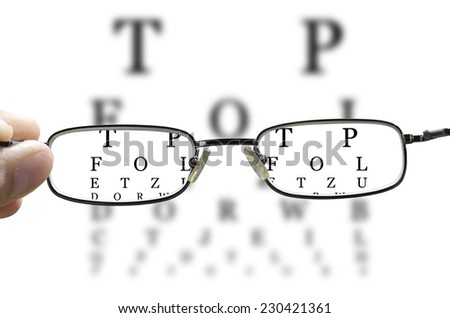 out of focus eye test and a hand holding glasses correcting the vision horizontal - stock photo