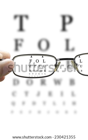 out of focus eye test and a hand holding glasses correcting the vision vertical