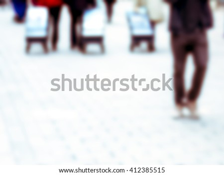 out of focus group of people on walkway with rolling suitcases - stock photo