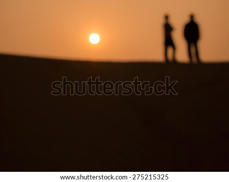 Out of focus image of 2 men at the desert in sunset time