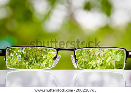 out of focus nature with eye glasses to look at amazing green - stock photo