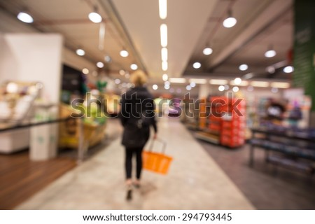 Out of focus shot from behind of a woman walking inside a supermarket starting her grocery shopping trip - stock photo