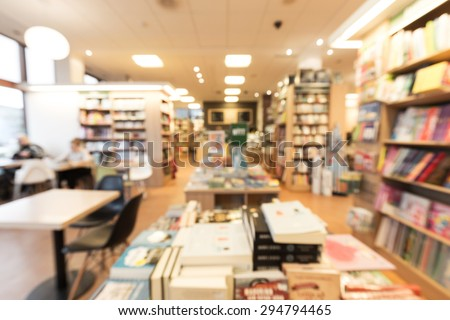 Out of focus shot from inside of a bookstore with cafe, books in shelves and on tables, customers reading magazines and drinking coffee to the left - stock photo