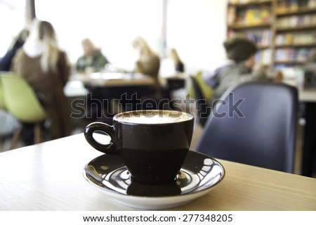 Out of focus shot inside a cafe, cup of cappuccino in the foreground and blurry guests at tables in the background - stock photo