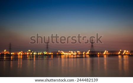 Out of focus the high voltage post at industry zone offshore and sea in twilight time    - stock photo