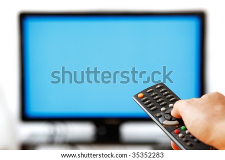 Out of focus TV LCD set and remote control in man's hand isolated over a white background. Blank screen.