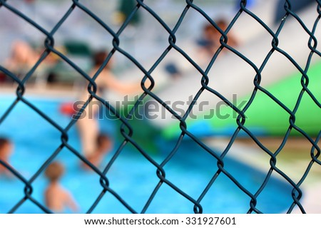 out of focus water park behind a fence
