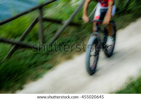 Out of focus with a man riding a mountain bike down a dirt road, Italy - stock photo