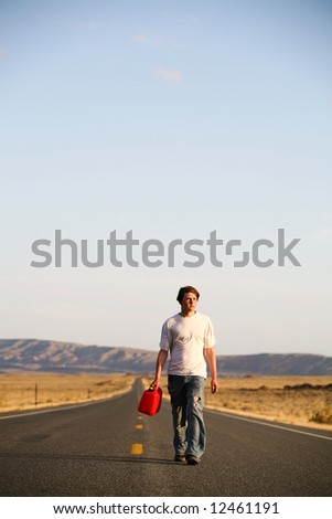 out of gas - male teenager walking down the highway with empty gas can. Blue sky with ample copyspace.