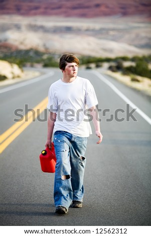 out of gas - male teenager with gas can walking on a mountain road in late sun