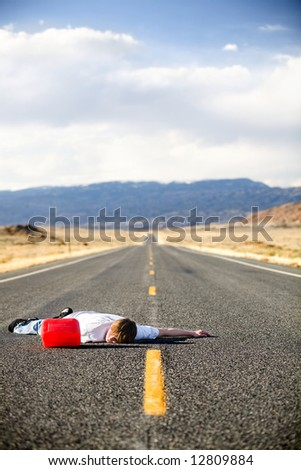 out of gas - teen male laying dead in the middle of a remote rural highway still clinging to red gas can - stock photo