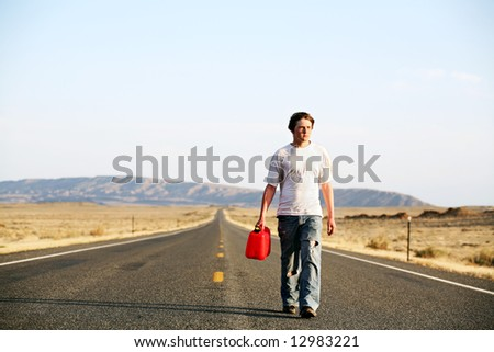 out of gas - teenager male walking down rural highway with empty red gas can - stock photo