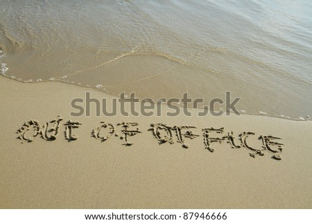 Out of office handwritten in sand on a beach