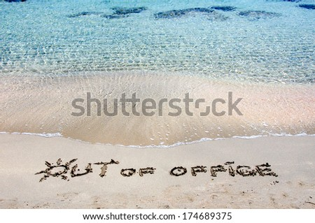 OUT OF OFFICE written on sand on a beautiful beach, blue waves in background .Relax concept image - stock photo