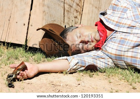 OUT WEST - A cowboy dead with arm in his hand - stock photo