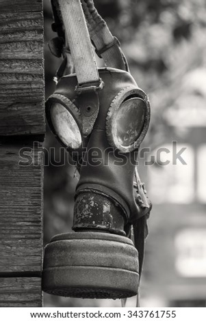 Outdated gasmask on a wooden wall in black white - stock photo
