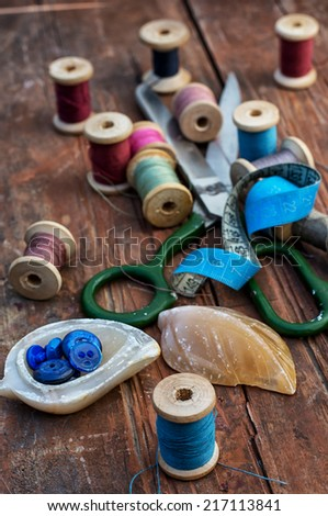 outdated sewing tools on wooden background