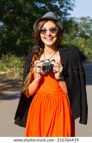 Outdoor autumn fashion portrait of young happy hipster girl posing at park,wearing trendy orange chiffon dress,black jacket,hat and sunglasses.Making photo and holding vintage camera.Vacation. - stock photo