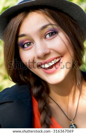 Outdoor autumn fashion portrait of young happy pretty stylish brunette woman with stunning smile and cute looks in park,wearing trendy orange chiffon dress,black jacket,and hat. Smiling and positive. - stock photo