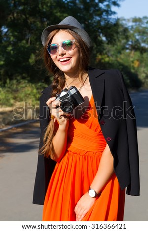 Outdoor autumn fashion portrait of young pretty smiling brunette woman photographer posing at park,wearing orange chiffon dress,black jacket,hat and sunglasses.Making photo and holding vintage camera. - stock photo