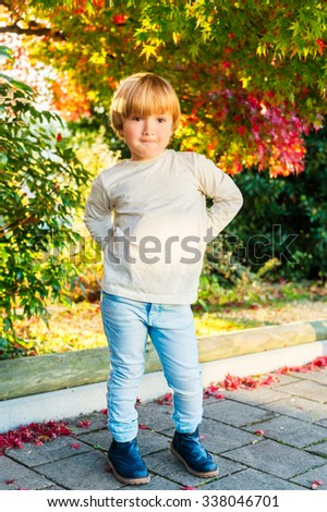 Outdoor autumn portrait of a cute little boy of 4 years old on a nice sunny day, wearing beige top, light blue denim jeans and boots - stock photo