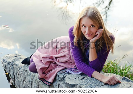 Outdoor autumn  portrait of beautiful girl above the lake surface - stock photo