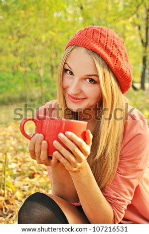 Outdoor autumn  portrait of beautiful girl with cup of tea
