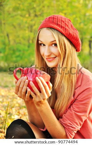 Outdoor autumn  portrait of beautiful girl with cup of tea - stock photo