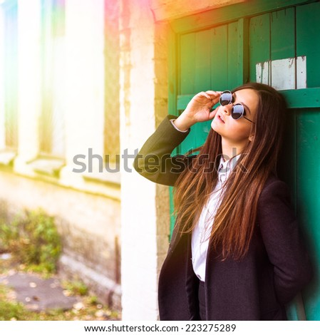 Outdoor autumn portrait of young pretty cute girl. Beautiful woman in black glasses posing near old building  - stock photo
