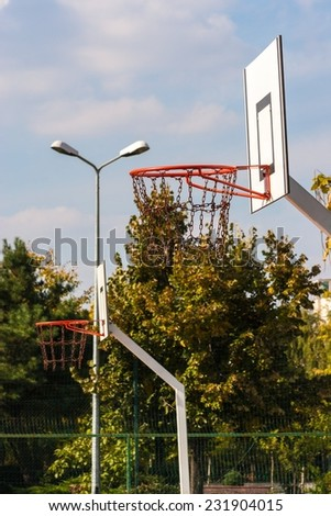Outdoor basketball baskets in a row with chain nets in a sunny day. - stock photo