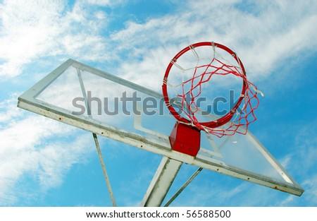 Outdoor basketball hoop against a blue sky - stock photo