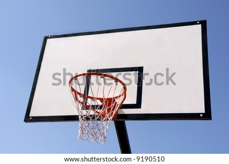 Outdoor basketball hoop against blue sky - stock photo