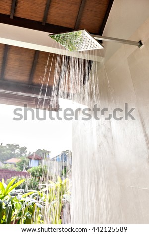 Outdoor bathing area, including working water shower and sunlight came from the outside - stock photo