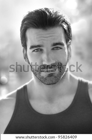 Outdoor black and white portrait of a classically good looking masculine man outdoors - stock photo