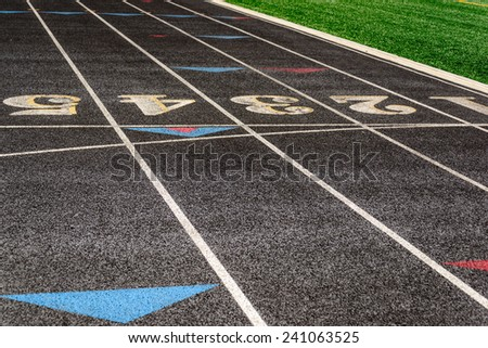 outdoor black running track with painted lane lines