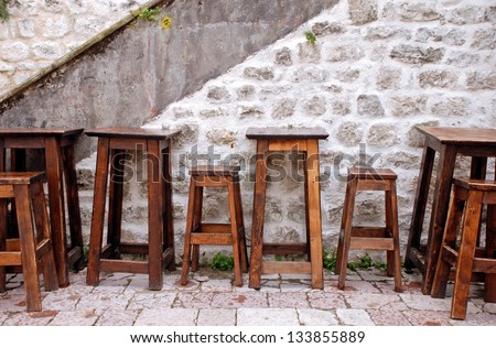 Outdoor cafe with wooden furniture and stone wall at small patio in old european town. Summer rain - stock photo